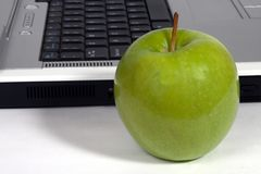 Green apple and laptop. Green apple beside a laptop on white background Stock Image