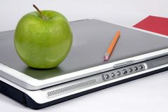 Green apple on laptop. Green apple on a laptop with pencil and red book on white backgrouns Royalty Free Stock Images