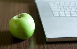 Green apple by laptop Royalty Free Stock Photos