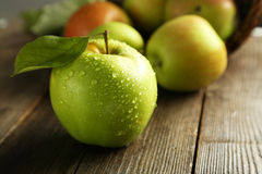 Green apple with leaf on brown wooden background. Stock Image