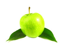 Green apple between leaves. On the white background Stock Photo