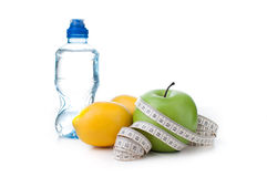 Green apple, lemon and bottle water with measuring tape Stock Photo