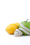 Green apple and lemon with measuring tape Royalty Free Stock Photo