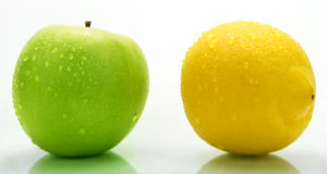 A green apple and a lemon with water drops. A clean green apple and a yellow lemon with some water drops Royalty Free Stock Photos