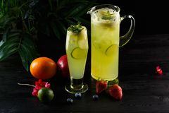 Green apple lemonade with lime in a jug and glass and fruits on a dark background royalty free stock image