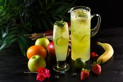 Green apple lemonade with lime in a jug and glass and fruits on a dark background stock images