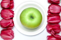 Green Apple lies on a white plate with white background next to multi-colored tulips. Closeup stock photo