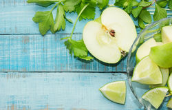 Green apple, lime cut and celery on blue wood Stock Images