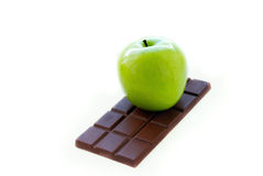 Green apple lying on the chocolate bar Royalty Free Stock Image