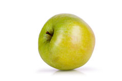 Green apple lying on its side on a white background Royalty Free Stock Photos