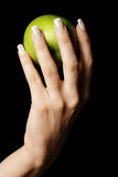 Green apple in manicured hand Stock Images
