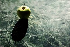 Green apple on a marble table royalty free stock photo