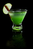 Green apple martini. Closeup of a green apple martini  on a black background garnished with an apple slice and a cinnamon stick Royalty Free Stock Photos