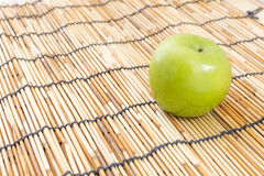 Green apple on mat Stock Images