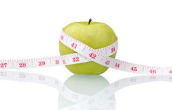 Green apple with measure tape Stock Photos