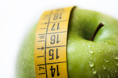 Green apple with measure tape. On white background Stock Photos