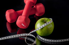 Fit. Green apple, measurement and dumbbells on black Stock Photo