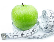 Green Apple with measuring tape. On white background stock photography