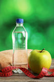 Green apple with measuring tape and bottle of water on grey wooden background. Royalty Free Stock Photos