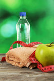 Green apple with measuring tape and bottle of water on the grey wooden background Royalty Free Stock Image