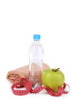 Green apple with measuring tape and bottle of water isolated on white. Royalty Free Stock Photos