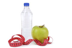 Green apple with measuring tape and bottle of water isolated on white. Royalty Free Stock Image