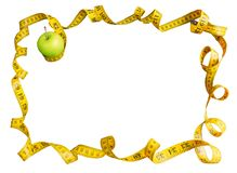 Green apple and measuring tape with centimeters and inches as a frame isolated on white background royalty free stock image