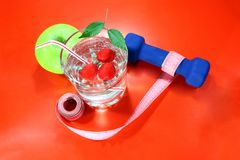 A green apple with a measuring tape, dumbbells. A delicious home made drink with fresh berries in a glass. Royalty Free Stock Image