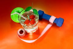 A green apple with a measuring tape, dumbbells. Stock Photography