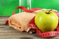 Green apple with measuring tape and glass of water on grey wooden background. Stock Photos