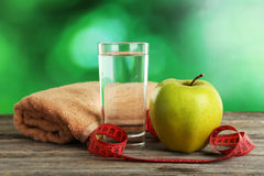 Green apple with measuring tape and glass of water on grey wooden background. Royalty Free Stock Photos