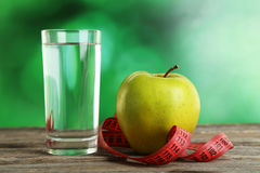 Green apple with measuring tape and glass of water on the grey wooden background Stock Photos