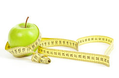 Green apple with a measuring tape and heart symbol isolated Royalty Free Stock Images