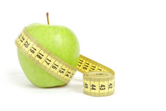 Green apple with a measuring tape and heart symbol isolated Stock Photos