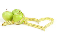 Green apple with a measuring tape and heart symbol isolated Stock Image
