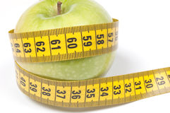 Green Apple with measuring tape, isolated on white Royalty Free Stock Images