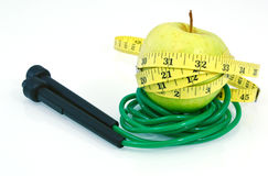 Green apple with measuring tape and jump rope on white background royalty free stock photos