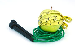 Green apple with measuring tape and jump rope on white background Stock Photos