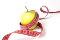 Green apple and measuring tape on white background stock photography