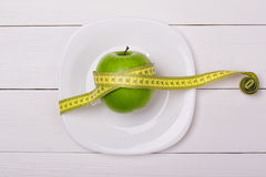 Green apple with measuring tape on a plate. Royalty Free Stock Photography