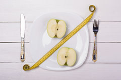Green apple with measuring tape on a plate with knife and fork. Sale, percent. Royalty Free Stock Images