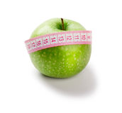 Green apple and measuring tape of the tailor Stock Photography
