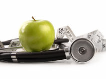 Green apple and measuring tape on white Royalty Free Stock Photography