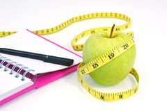 Green apple with measuring tape on white background. Stock Photo