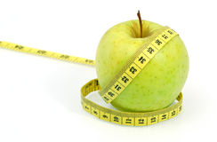 Green apple with measuring tape on white background. Royalty Free Stock Image