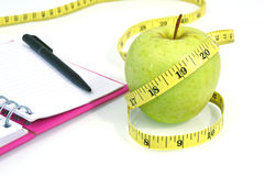 Green apple with measuring tape on white background. Royalty Free Stock Images