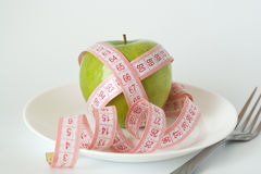 Green apple and measuring tape on a white plate Stock Photography