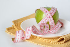 Green apple and measuring tape on a white plate Stock Images