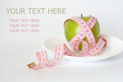 Green apple and measuring tape on a white plate Royalty Free Stock Photo