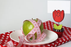 Green apple and measuring tape on a white plate Royalty Free Stock Images